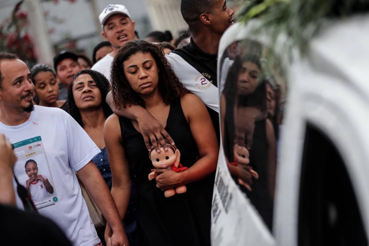 Kuolleen 8-vuotiaan pikkutytön vanhemmat seurasivat ruumisautoa hautajaispaikalle Rio de Janeirossa 22. syyskuuta.