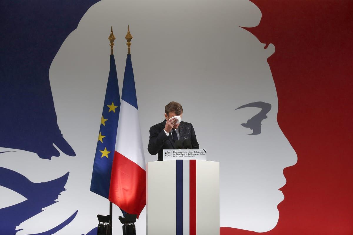 Ranskan presidentti Emmanuel Macron pyyhkii kasvojaan ennen puhettaan muistotilaisuudessa, jossa kunnioitettiin Pariisin veitsihyökkäyksessä surmansa saaneita poliiseja.