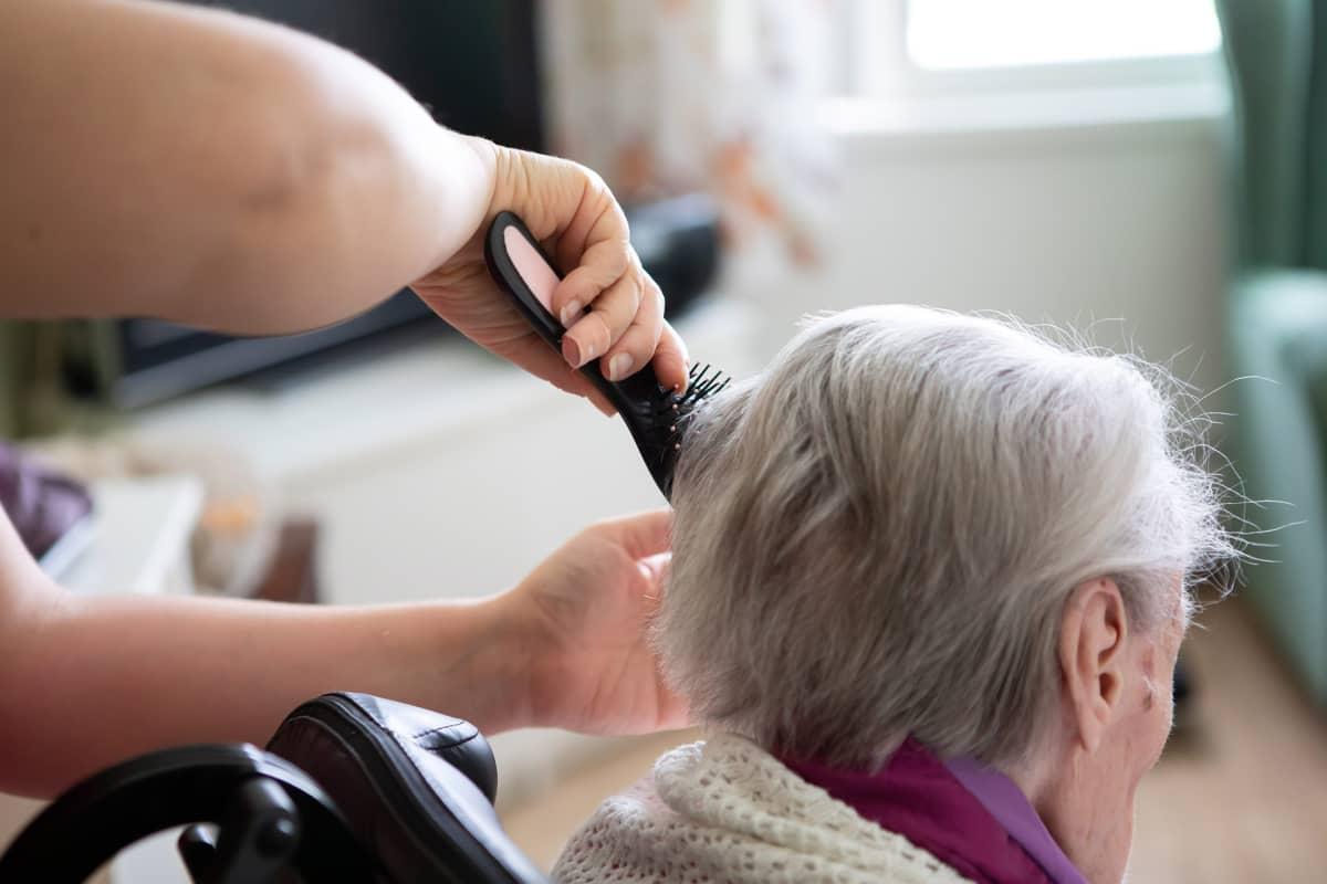 Lähihoitaja harjaa potilaan hiuksia.
