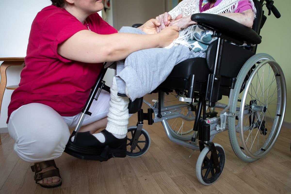 Lähihoitaja pitelee potilaan käsistä.