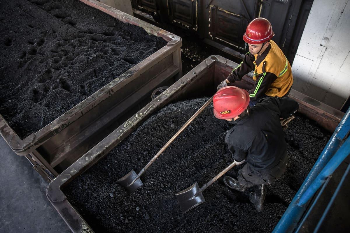 Kiinalaiset kaivostyöläiset lapioivat hiiltä Diantoussa, Kiinassa.