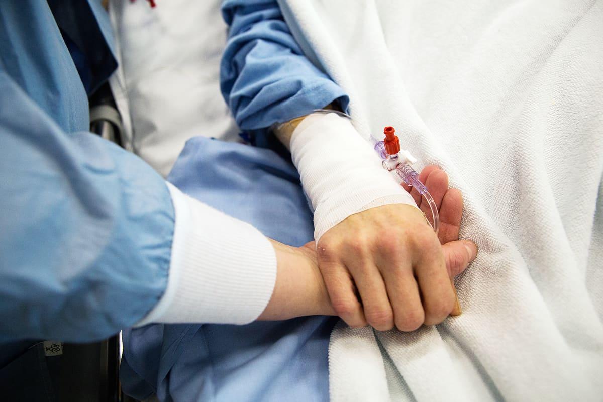 Hoitaja pitää potilasta kädestä.