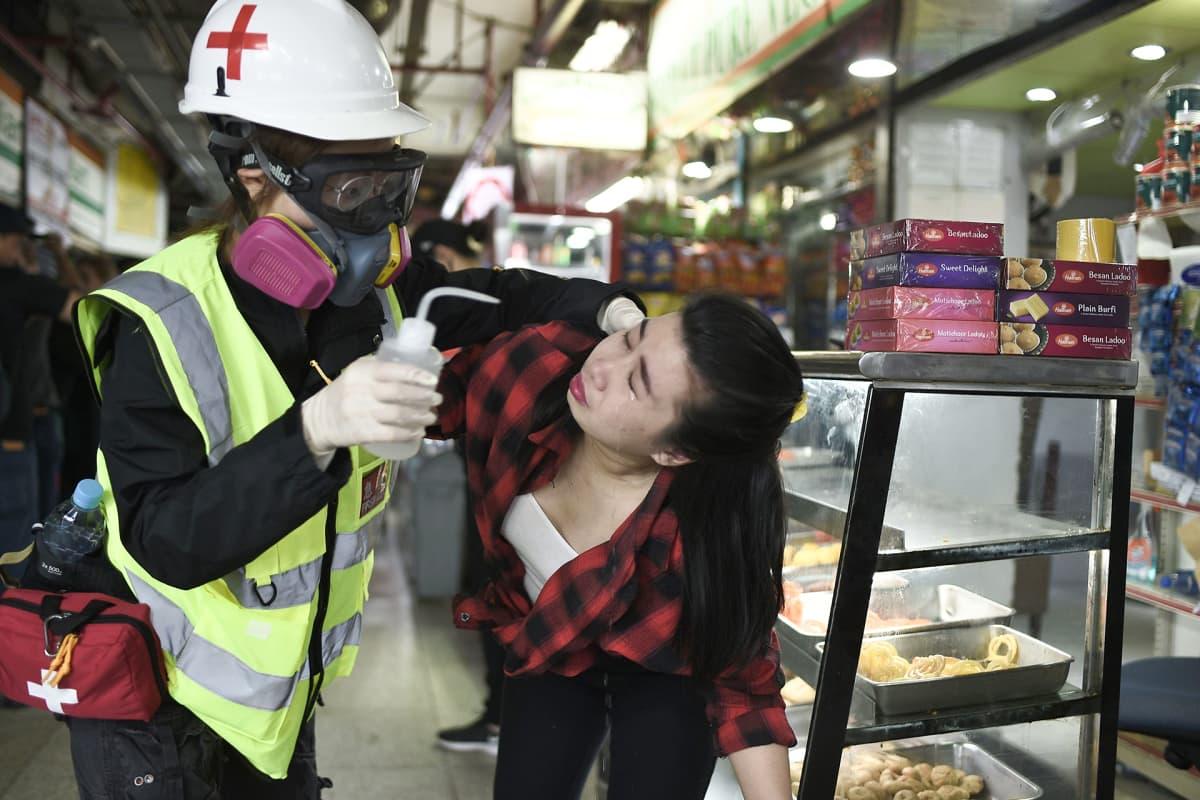 Ensiapuhenkilö auttaa naista joka joutui poliisien kyynelkaasuiskun kohteeksi.
