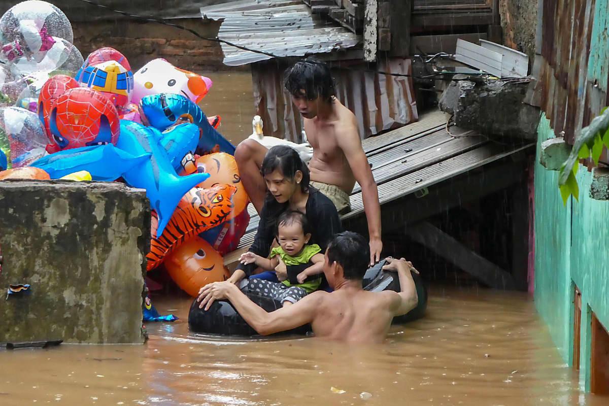 Lapsi kumirenkaan päällä tulvavedessä, perhe vierellä