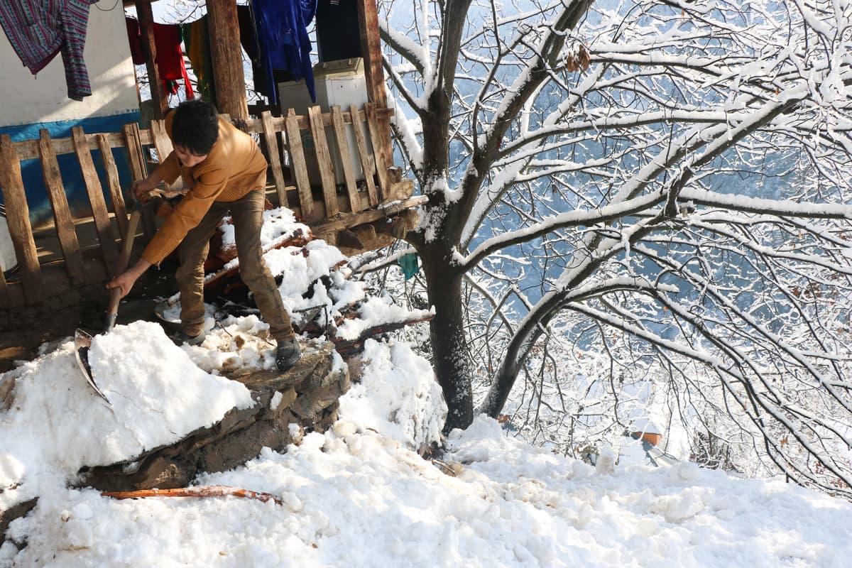 Poika lapioi lunta, lumivyöryn jäljiltä.