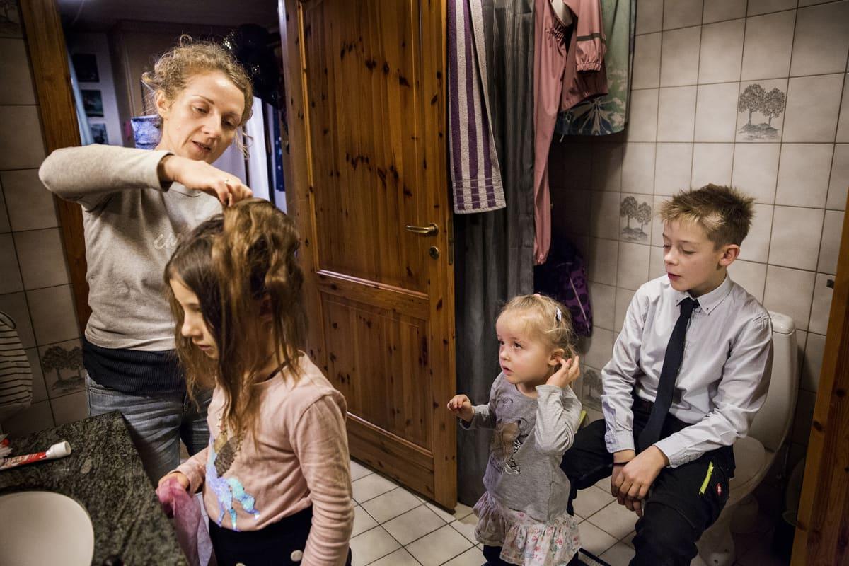 perhe vessassa, äiti laittaa tyttären tukkaa
