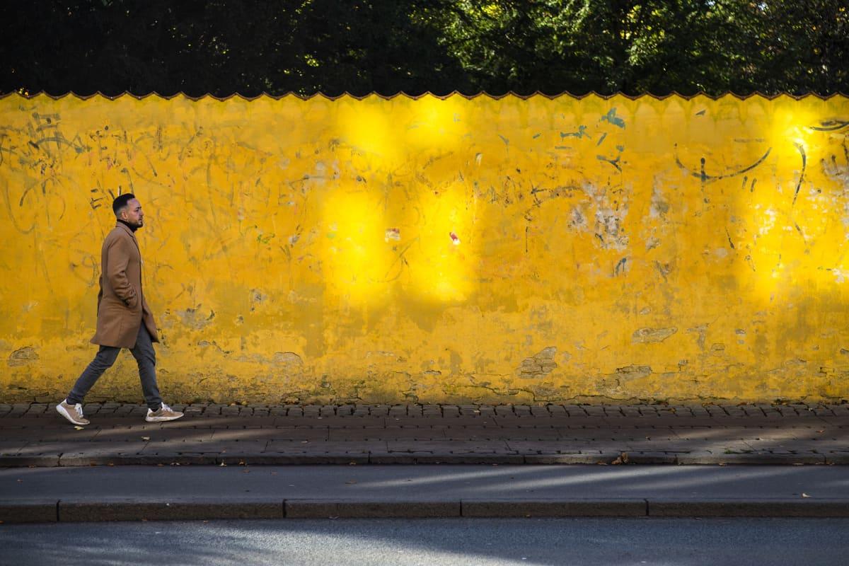 Rachid Moutiq kävelee keltaisen seinän vierellä.