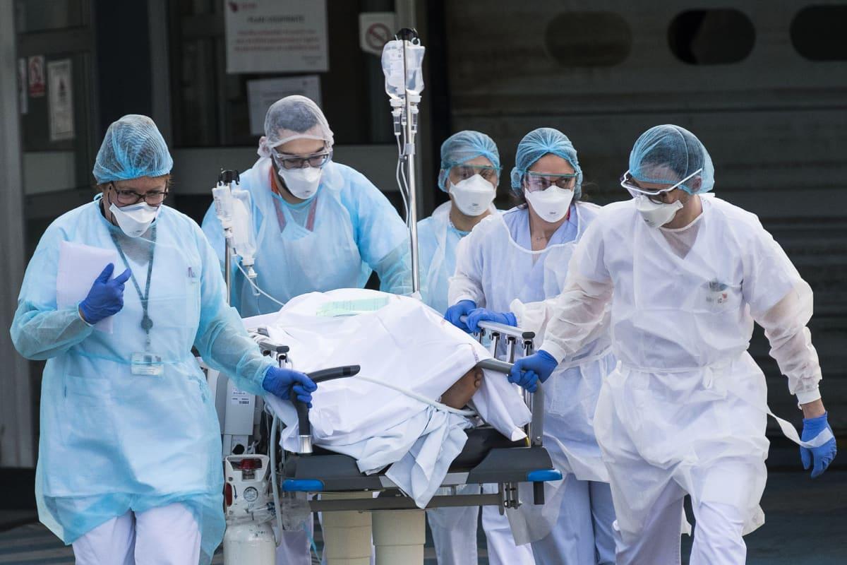 Sairaalan henkilökunta suojavarusteissa työntää koronaviruspotilasta paareilla 17. maaliskuuta Ranskassa.
