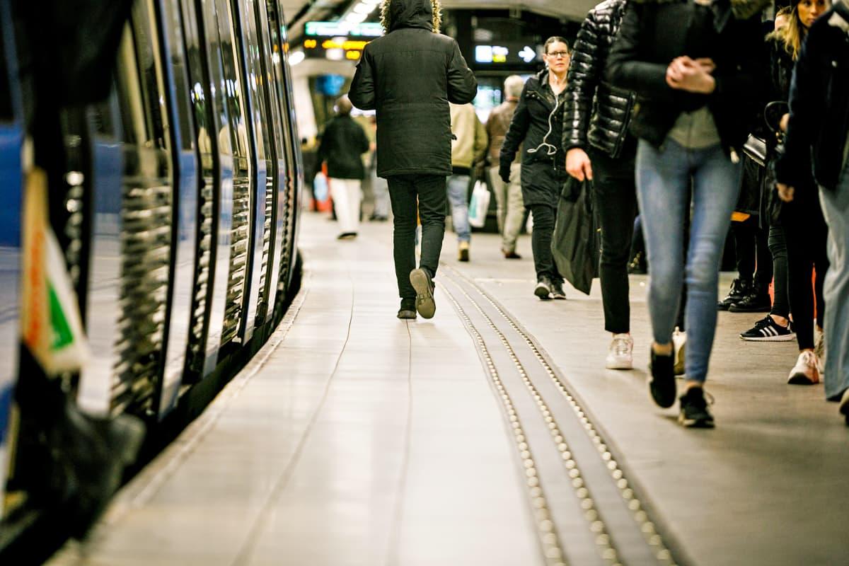Ihmisiä kävelee metrolaiturilla.
