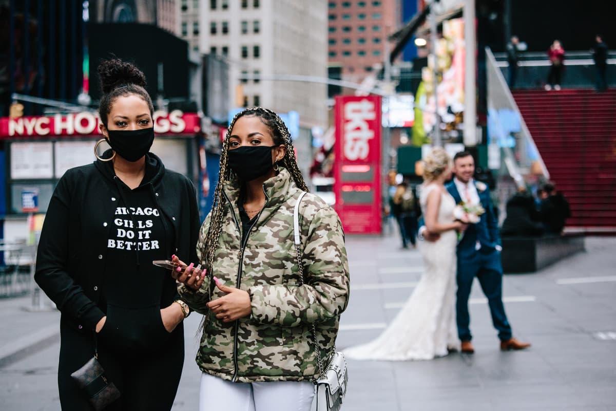 Kaksi naista etualalla pukeutuneena hengitysmaskeihin ja taustalla näkyy hääpari joista otetaan hääkuvia.