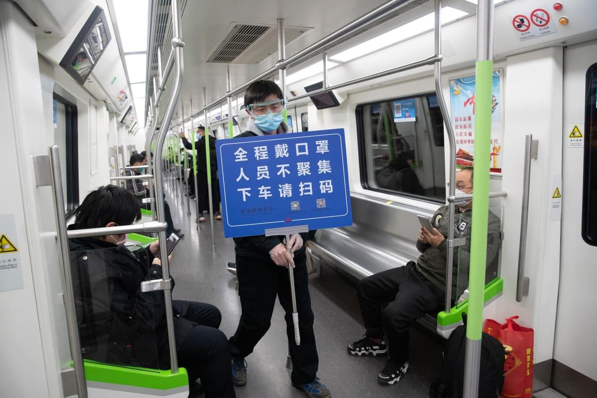 Wuhanin metron työntekijä kantaa ohjekylttiä.
