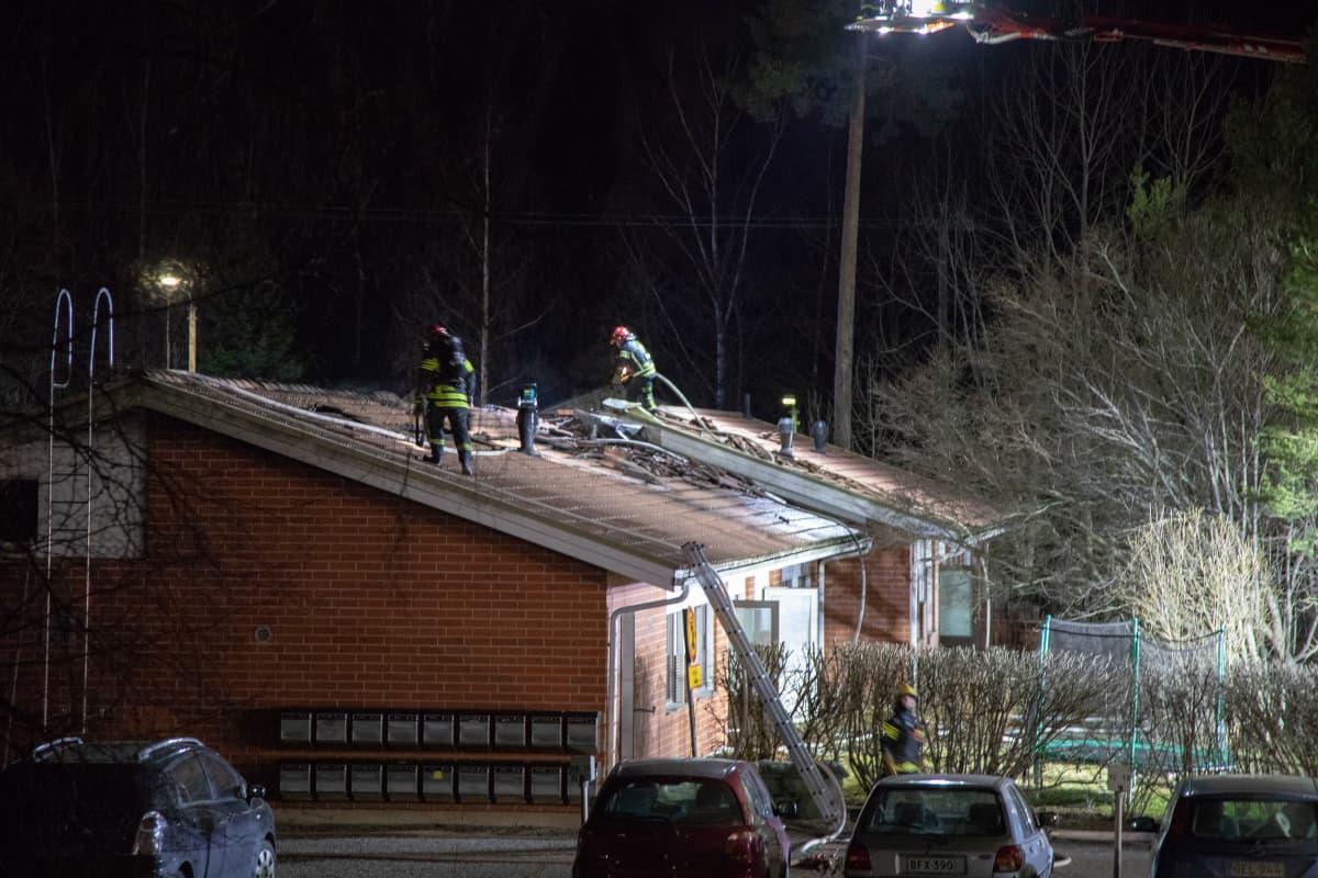 Palomiehiä rivitalon katolla sammuttamassa paloa.
