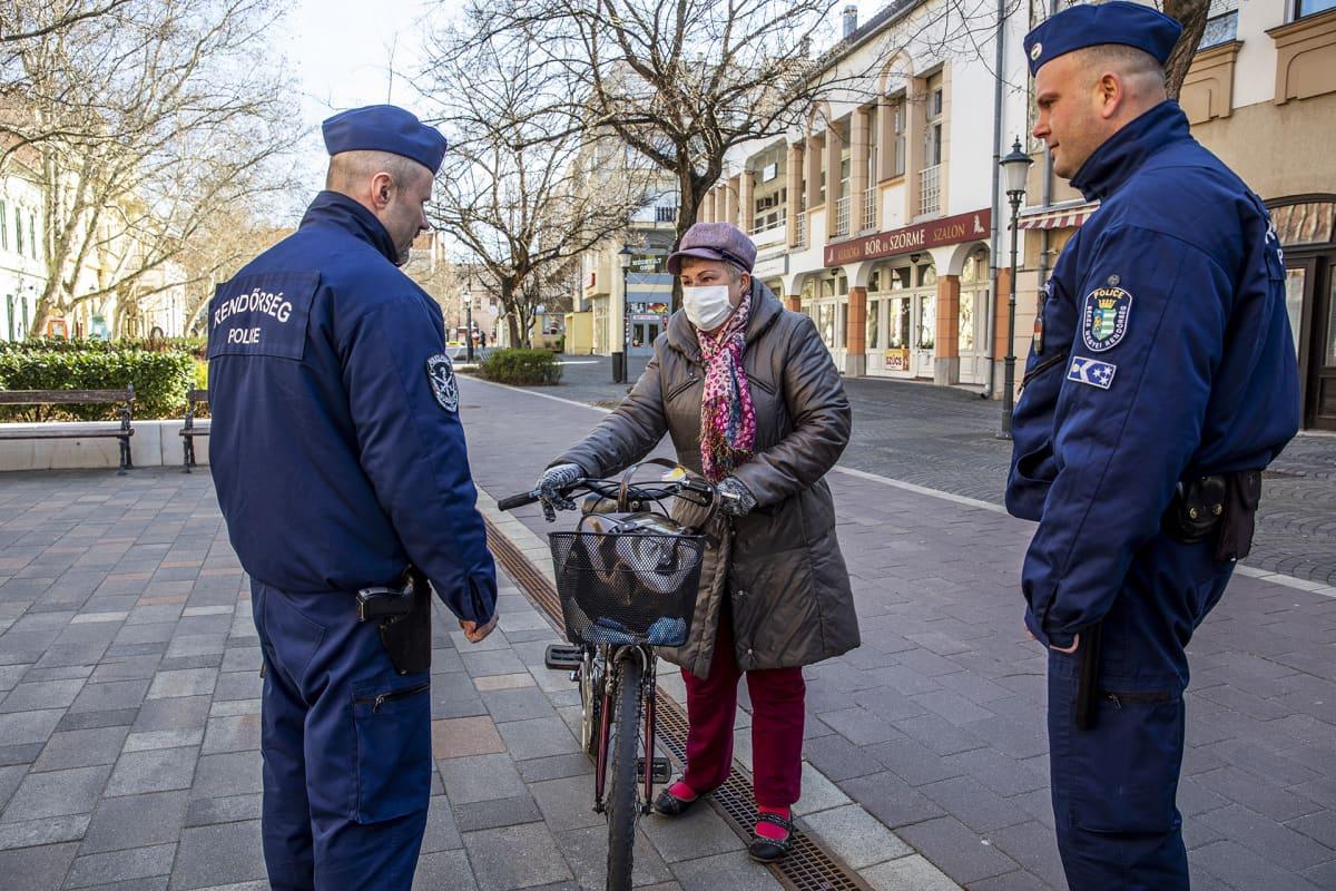 Poliisit keskutelivat polkupyörällä liikkeellä ollen naisen kanssa muuten autiolla kadulla Bekescsabasas Unkarissa.