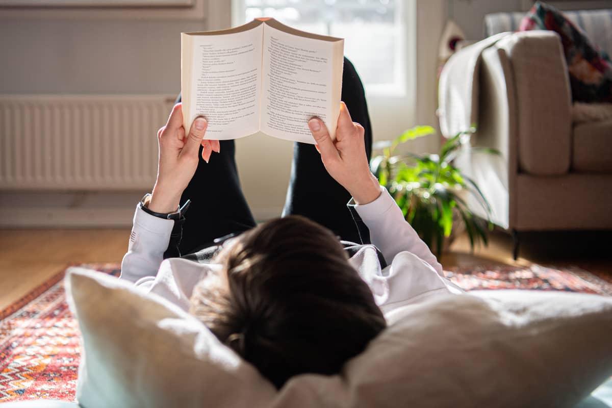 Nainen lukee kirjaa lattialla.
