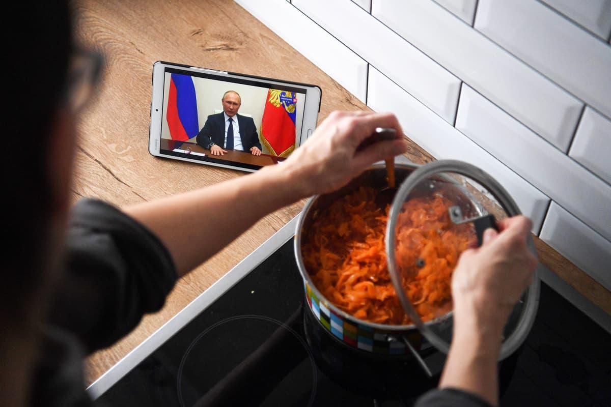 Venäläisnainen laittaa ruokaa ja katsoo samalla kännykästä presidentti Vladimir Putinin puhetta.