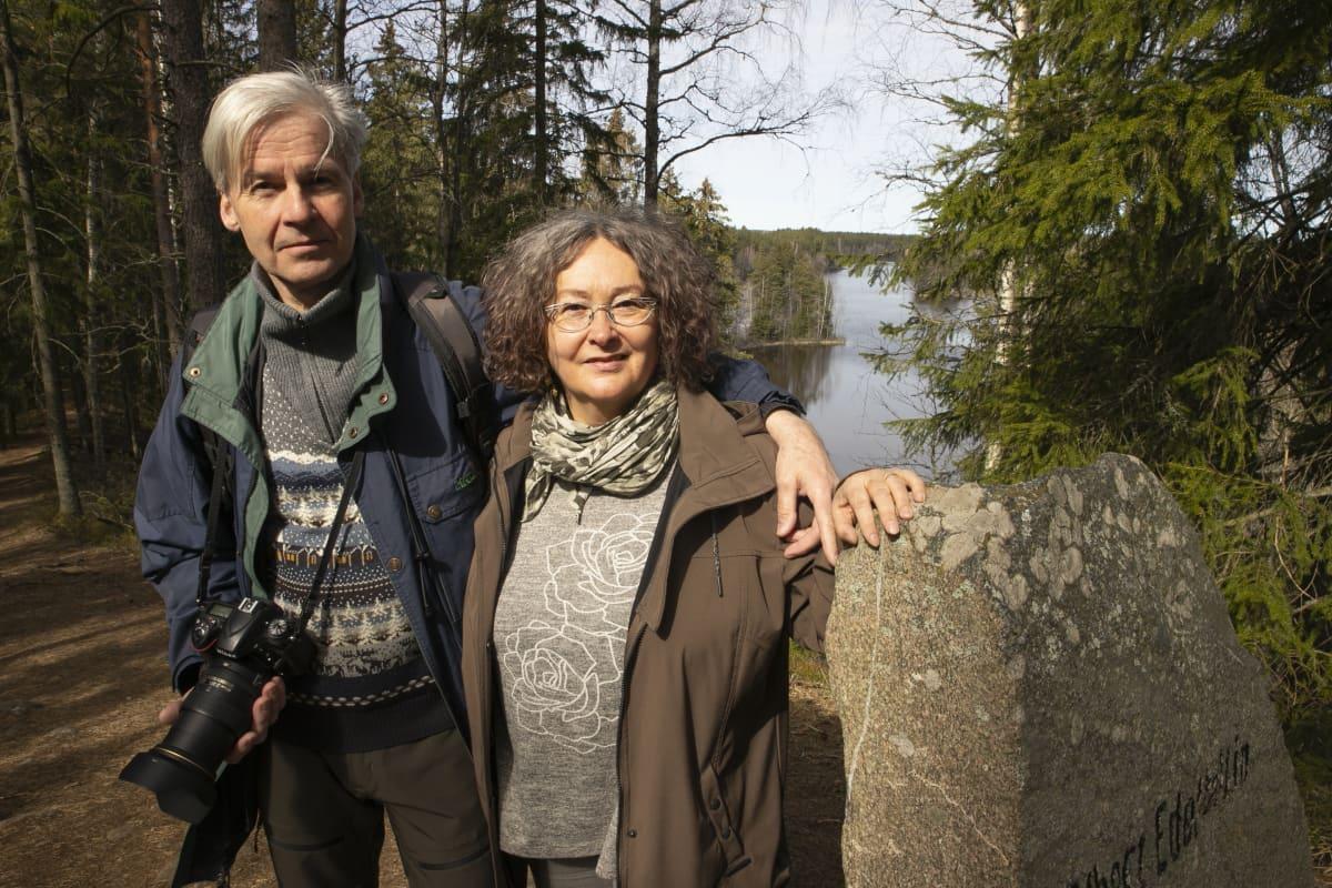 Pariskunta seisoo vierekkäin luonnossa ja katsoo kameraan.