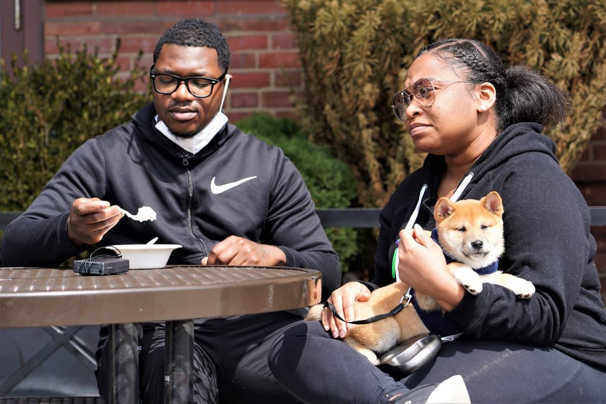 Roslyn Jones (oikealla) ja Jeffrey Hill ulkoiluttavat Coby-koiranpentuaan Baltimoren kaupunkisataman alueella.