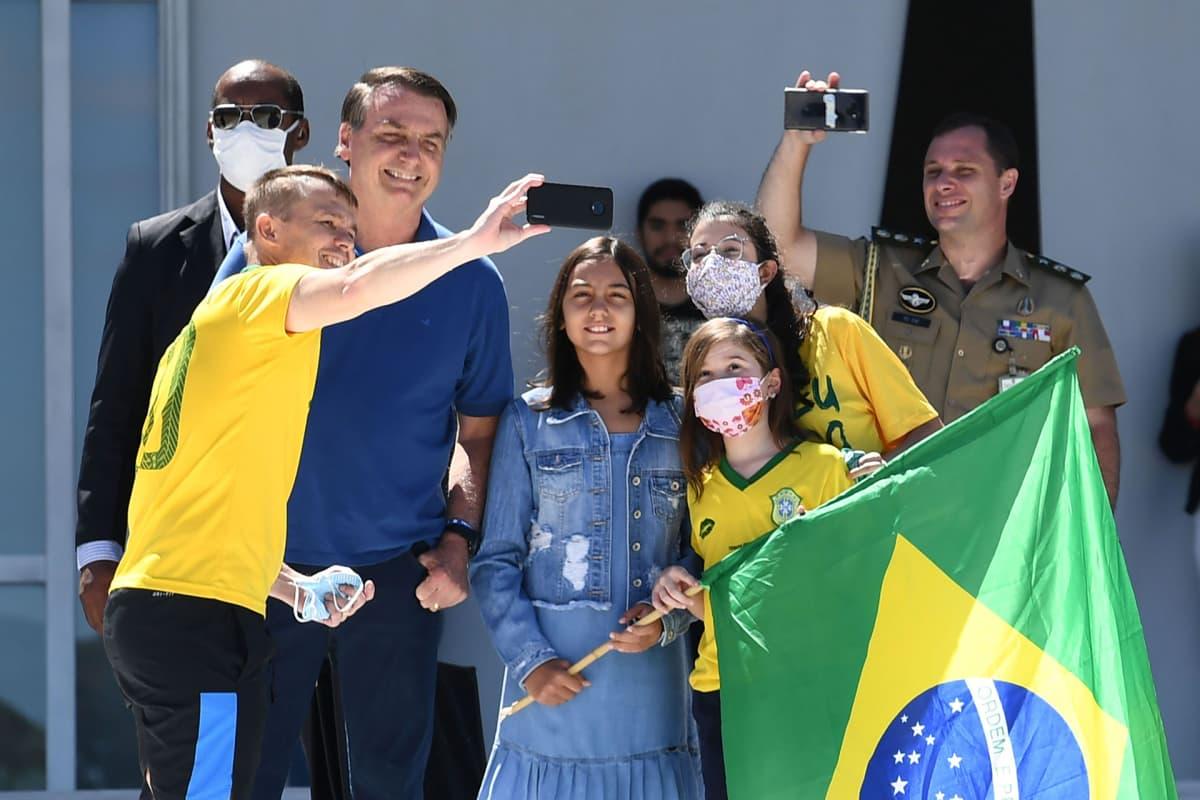 Jair Bolsonaro poseerasi selfiessä kannattajiensa kanssa Planalto-palatsin edustalla Brasiliassa sunnuntaina.