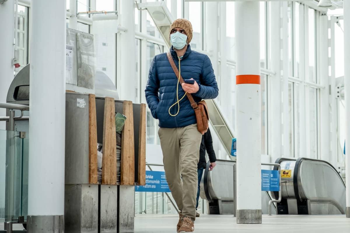Mies kävelee Vuosaaren metroasemalla hengitysmaski kasvoillaan.