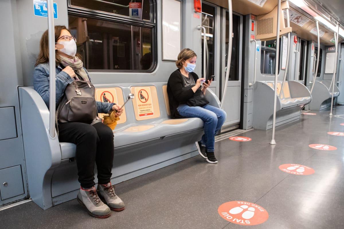 Matkustajat istuvat metrossa turvavälin päässä, turvaväliä osoittavia merkkejä Milanon metron lattiassa ja penkeillä