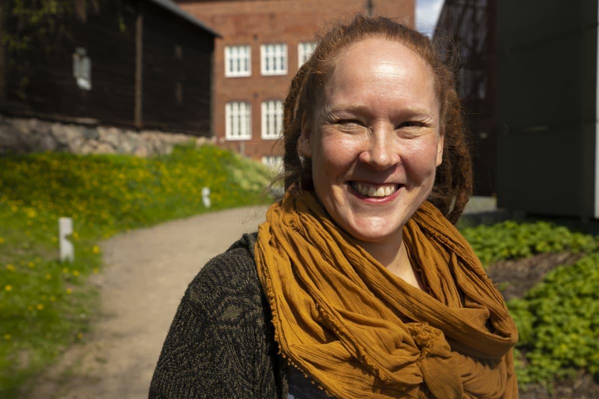 Hymyilevä nainen seisoo auringonpaisteessa ja katsoo kameraan.
