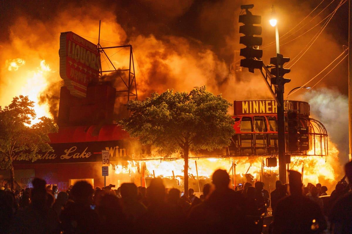 Protestoijat katselevat tulen vallassa olevaan viinakauppaa.