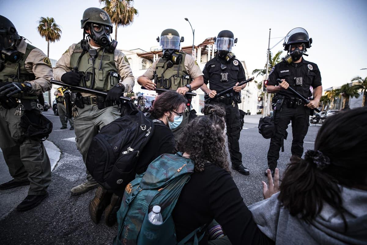 Protestoijat istuvat maassa ja poliiseja seisoo heidän ympärillään.