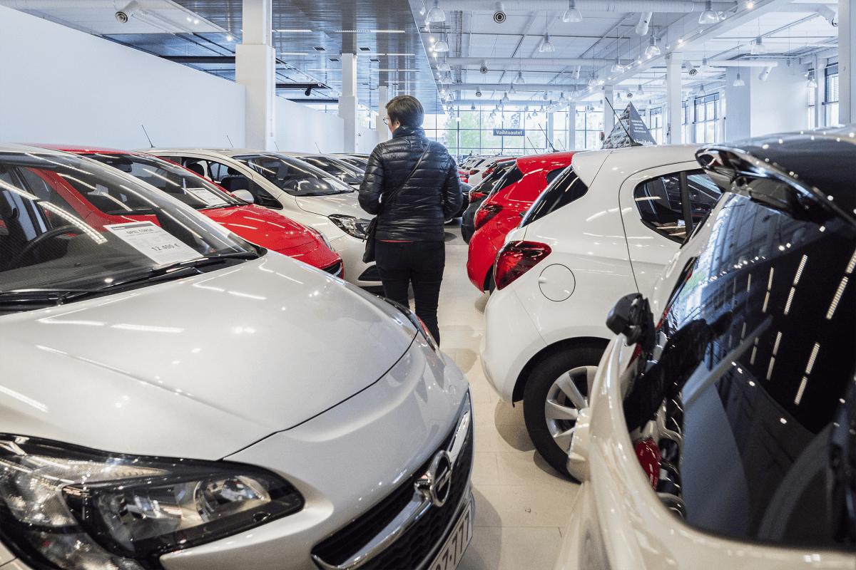 Nainen katselemassa käytettyjä autoja autoliikkeessä.