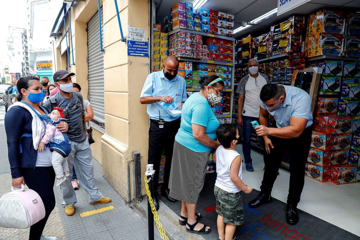 Asiakkaiden lämpö mitattiin marketin ovella São Paulossa 10. kesäkuuta.