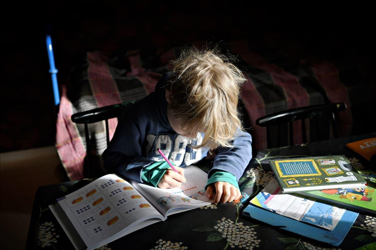 Koulusta koronaviruksen vuoksi kotiin jäänyt lapsi opiskelee kotona Helsingissä maaliskuussa 2020.