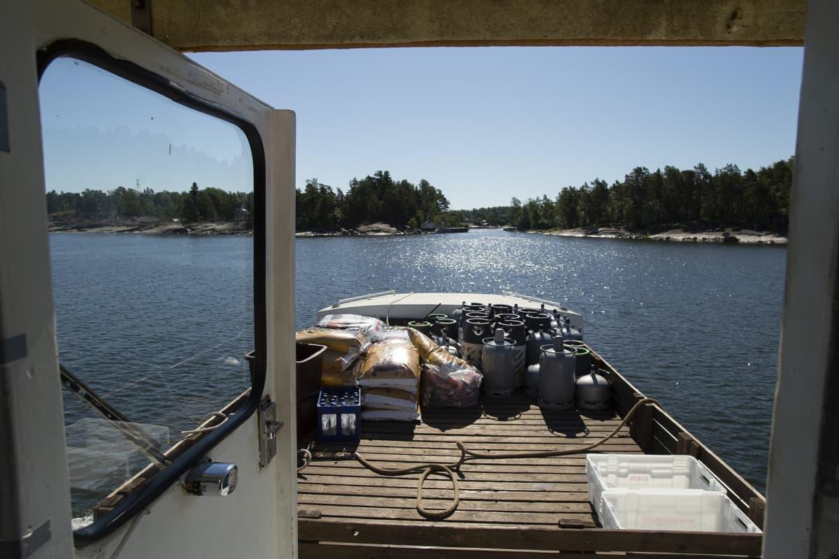 Saaristoa komentosillalta katsottuna, laivan kannella on kaasupulloja ja huussikuivikesäkkejä.