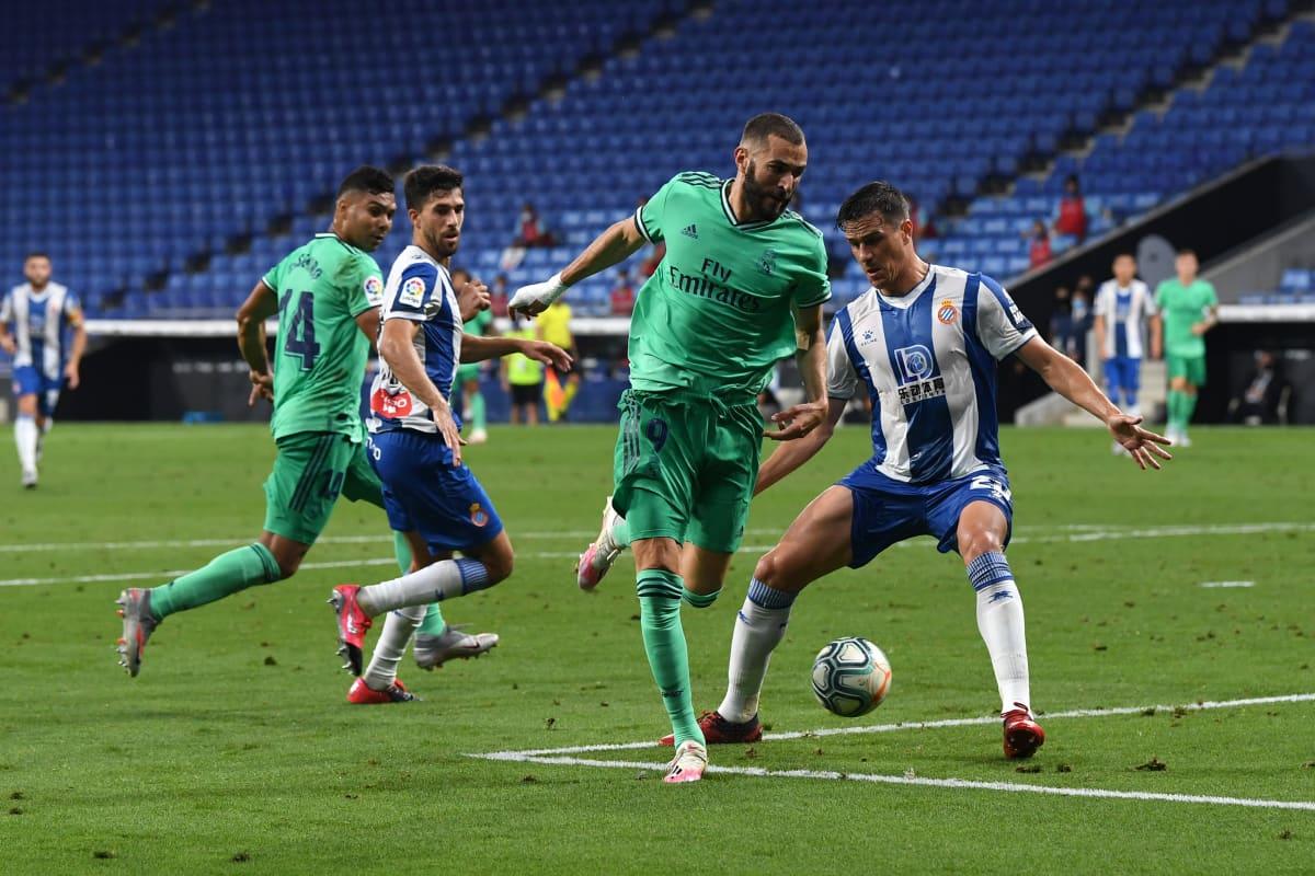 Karim Benzema syöttää pallon Casemirolle Espanyol-puolustajan jalkojen välistä.