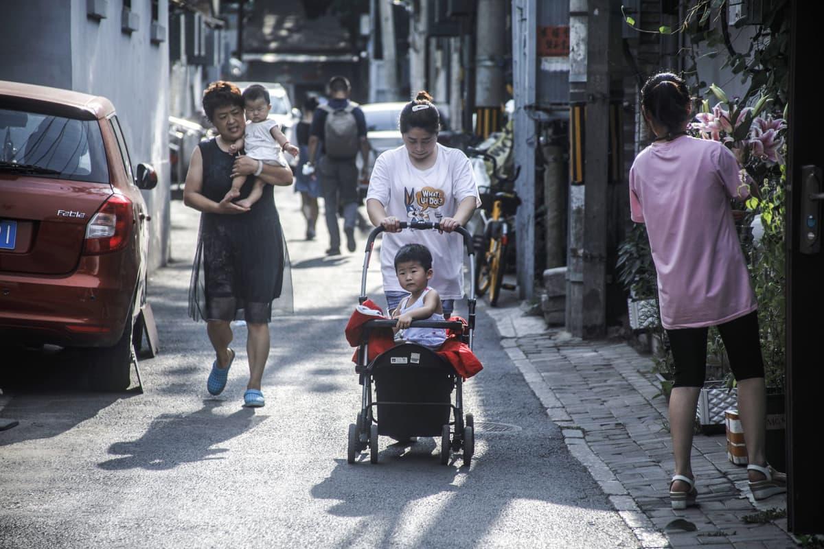 Naisia lastensa kanssa kadulla.