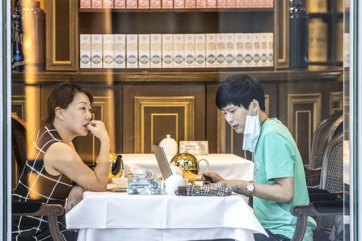 Pariskunta ravintolassa kuvattuna ikkunan läpi.