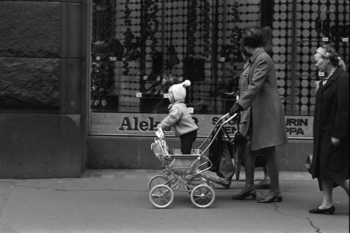 Aleksanterinkatu 13. Rattaissa seisovaa lasta työntävä nainen Aleksanterinkadulla kävelykatukokeilun aikaan vuonna 1970.