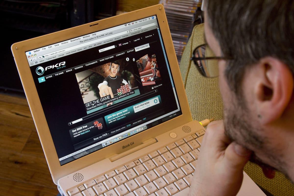 Mies pelaa nettipokeria kannettavalla tietokoneella.