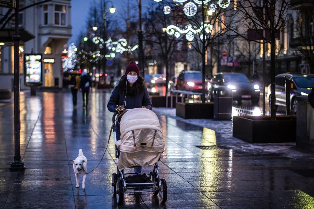Nainen työntää lastevaunuja jouluvaloilla koristellulla kadulla Vilnassa.