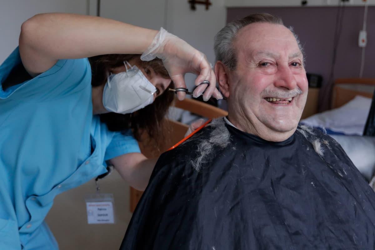 Vanhainkodin hoitaja leikkaa asukkaan hiuksia Chatelet'ssa, Belgiassa lokakuussa 2020.