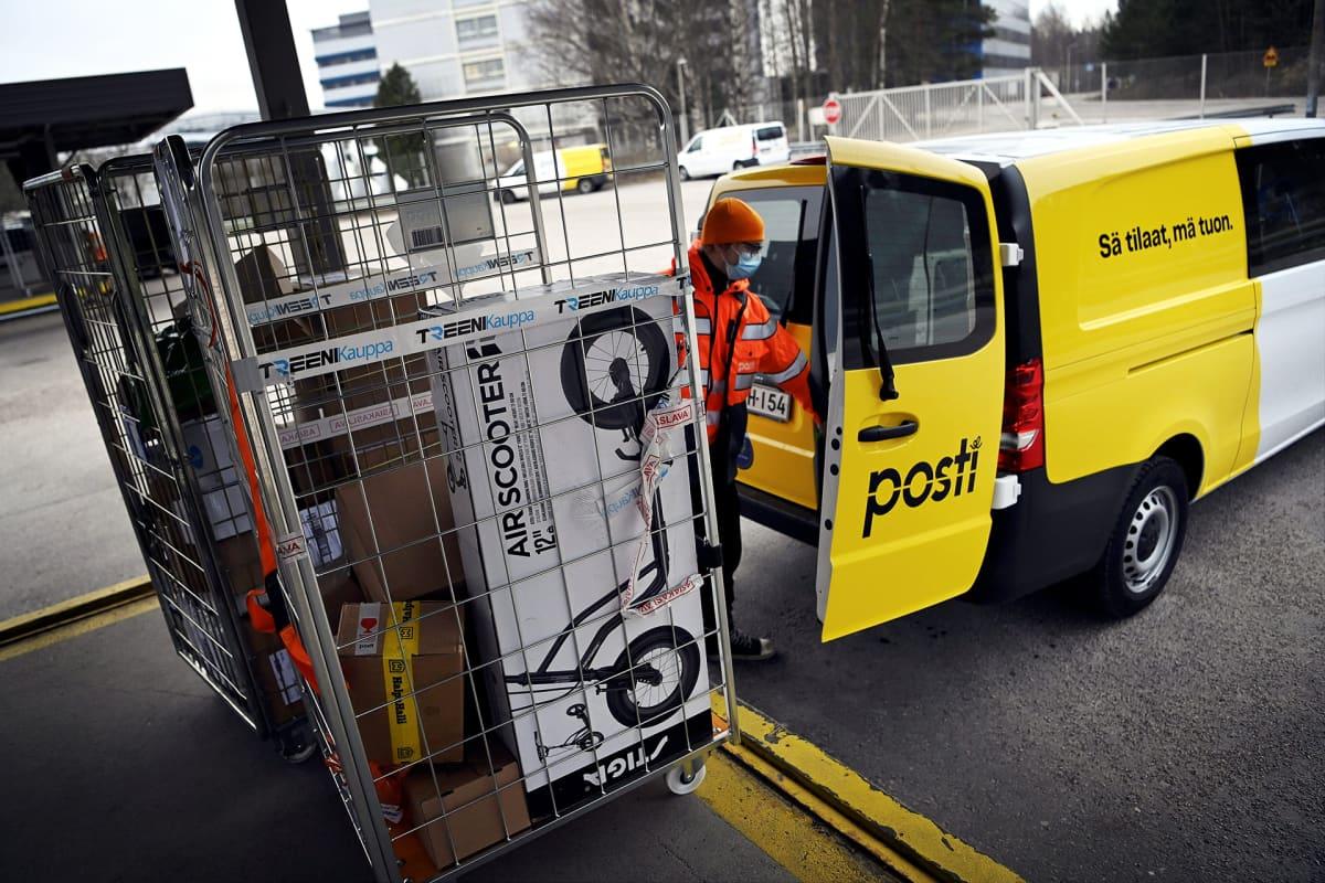 Postin työntekijä pakkaa paketteja kuljetusta varten