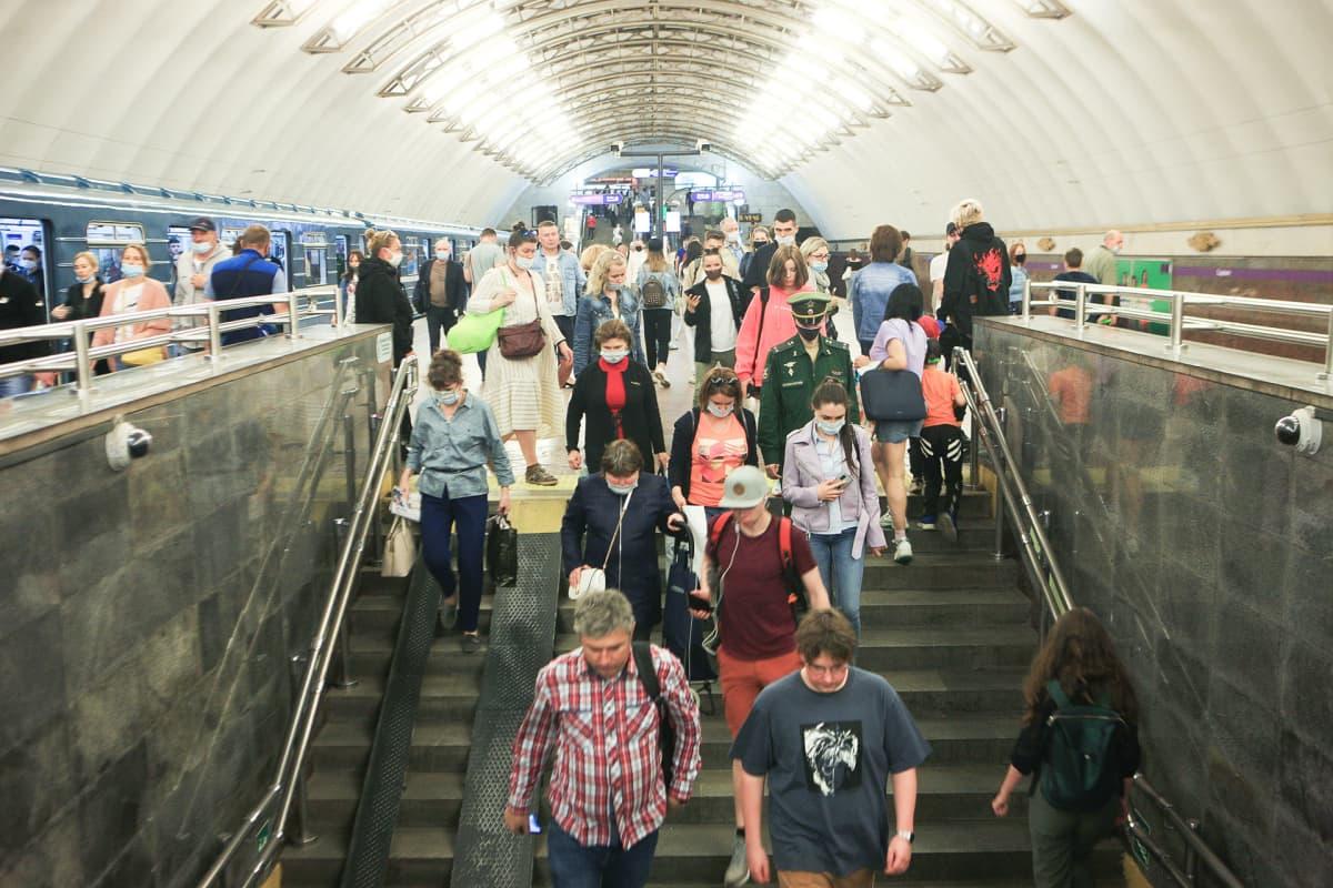 Ihmisiä metrolaiturilla.