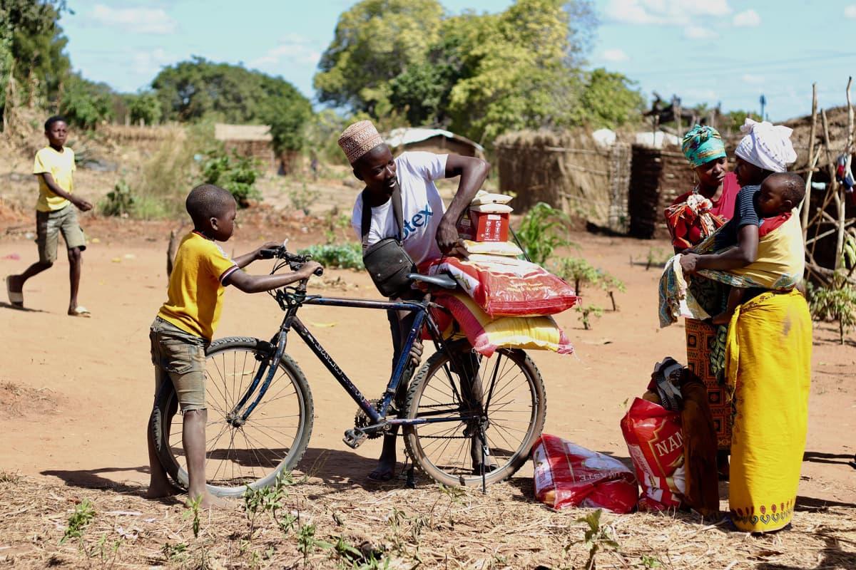 Mies lastaa juuri saamansa ruoka-apua pyörän selkään lähellä Montepuezin kaupunkia Cabo Delgadossa.
