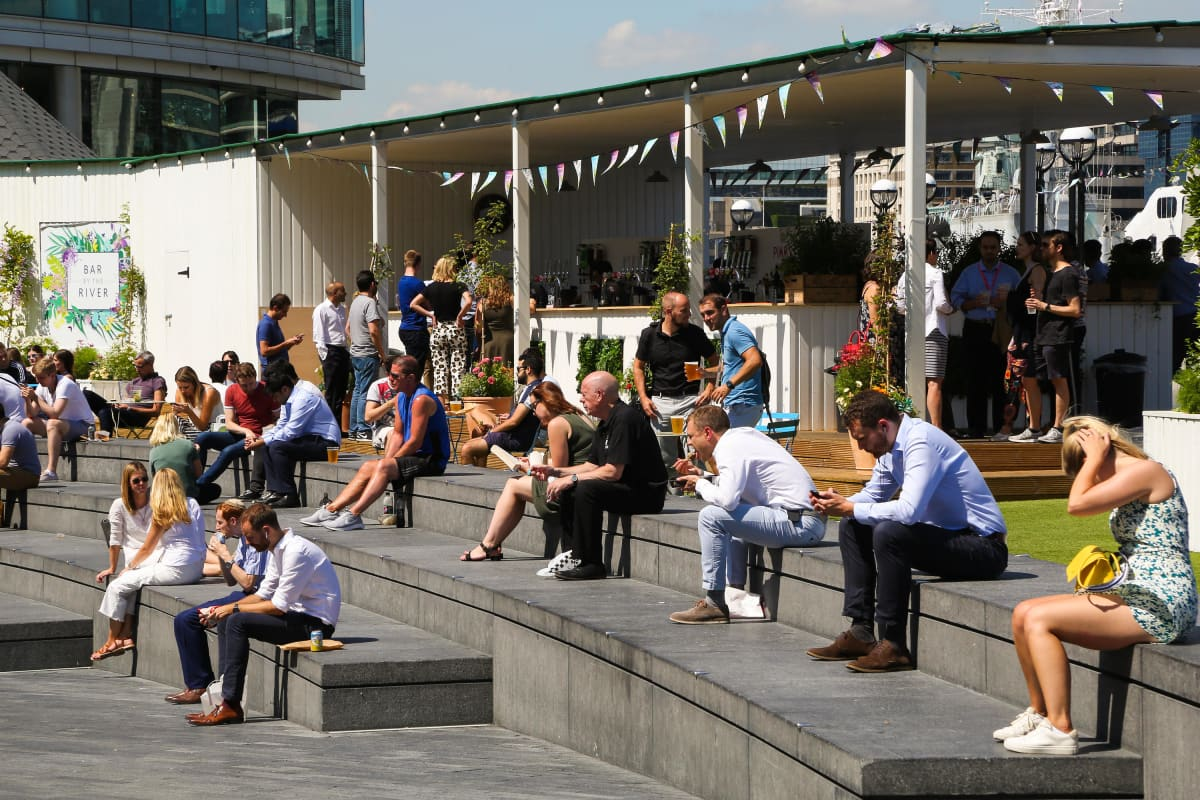 Ihmisiä puistossa istumassa