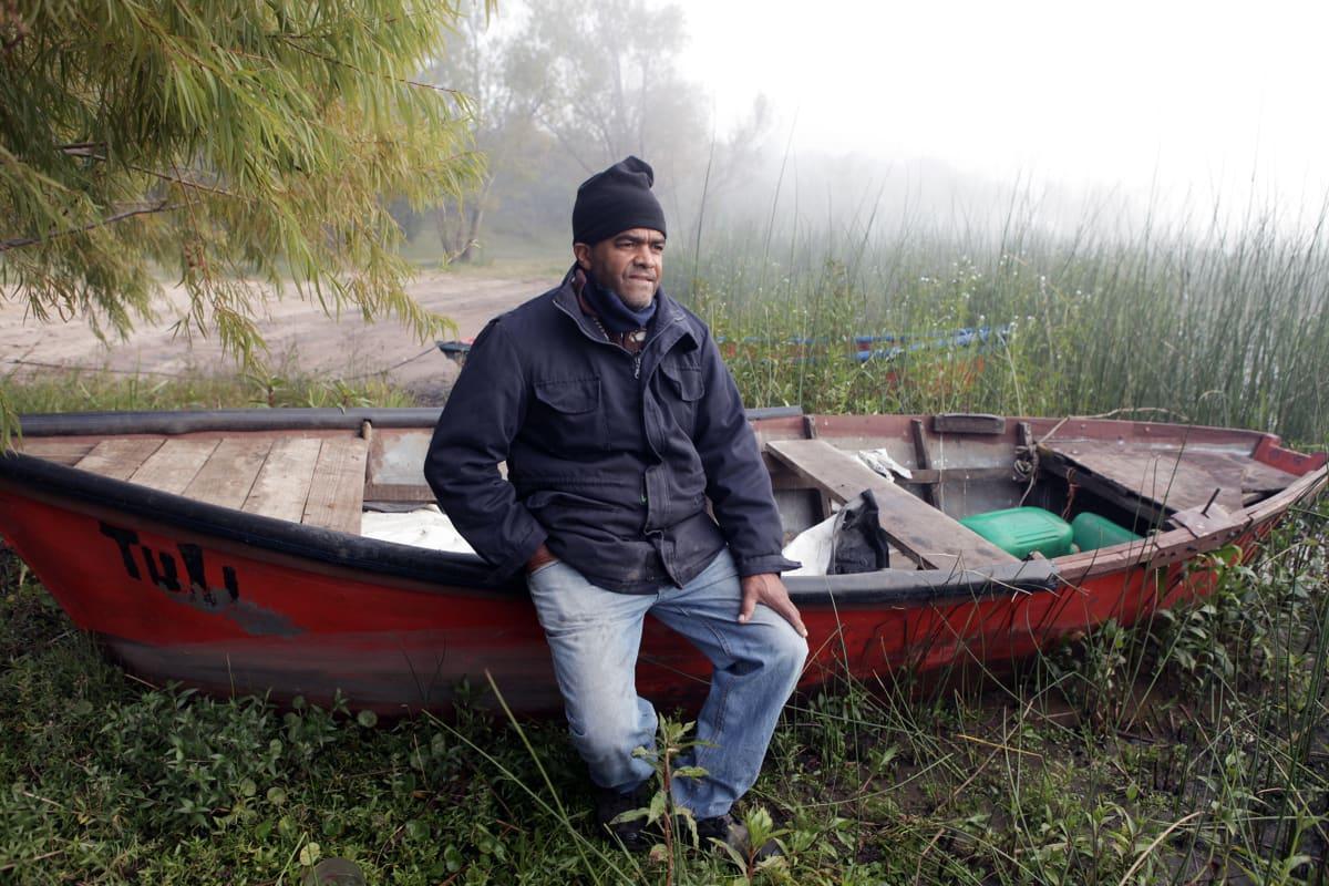 Kalojen tukkuostajan Felix Pereyran istuu veneen laidalla joen törmällä.