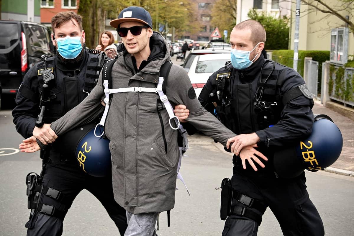 Kaksi poliisia taluttaa Querdenker-mielenosoittajaa kadulla Frankfurtissa