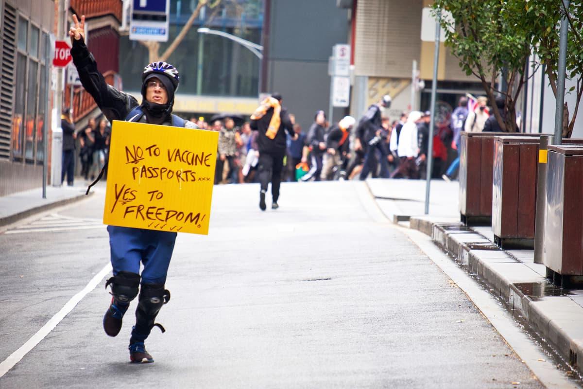 Koronarokotukisa ja -passeja vastustava mielenosoittaja kadulla Melbournessa.