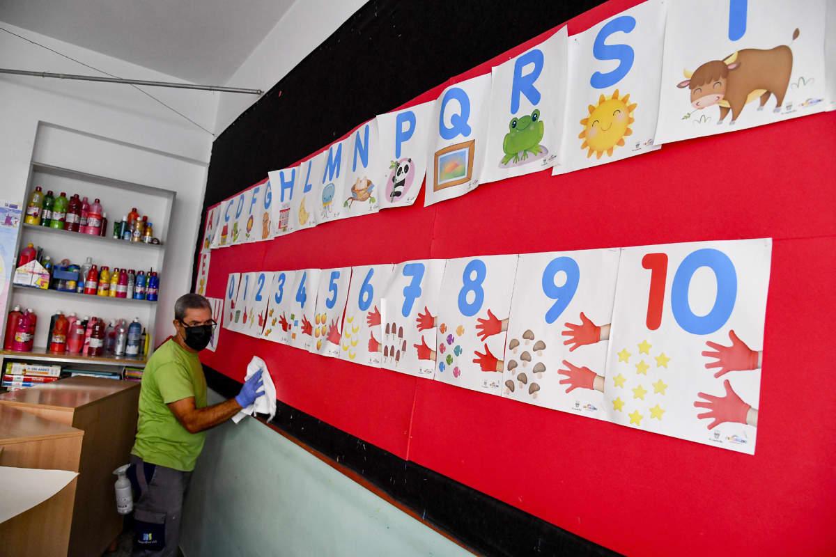 Napolin kunnan työntekijä puhdistaa pintoja lastentarhassa Napolissa kouluvuoden alkaessa 10 syyskuuta.