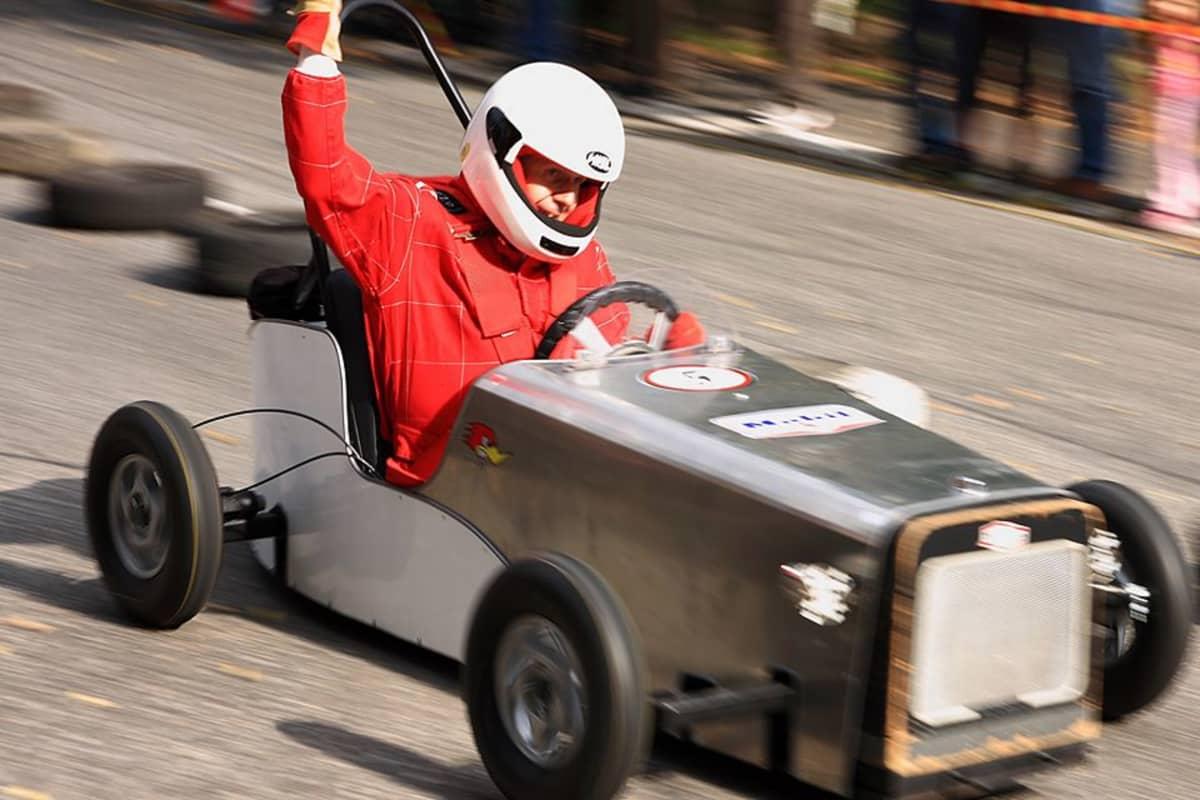 Punapukuinen mies ajaa hopeanvärisellä mäkiautolla