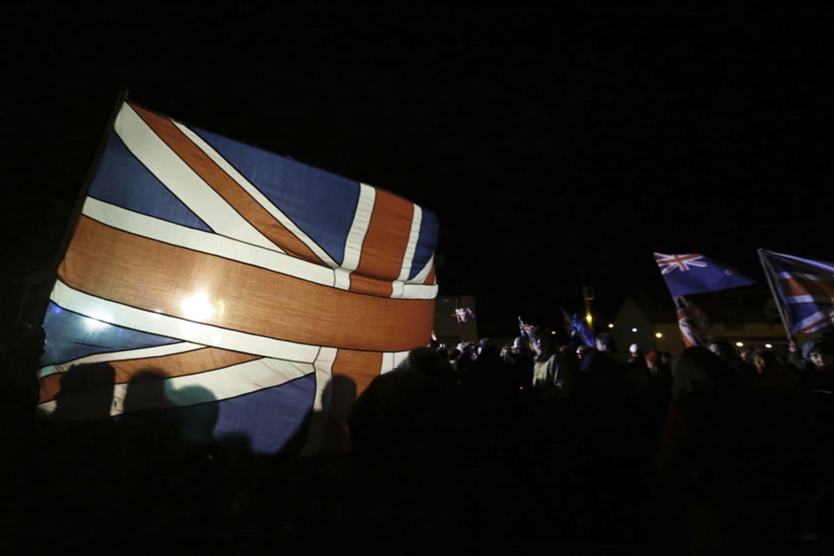 Väkijoukkoa pimeässä Britannian lipun loistaessa.