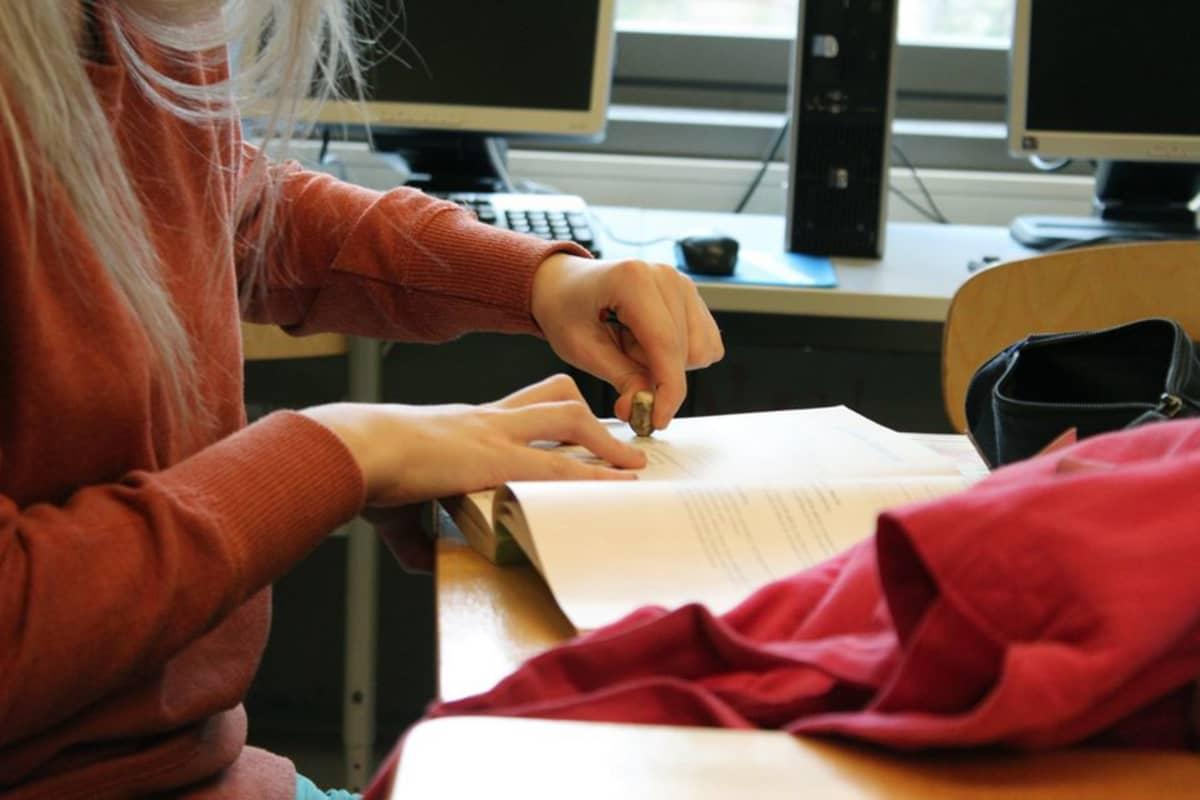 Oppilas pyyhekumi kädessä.