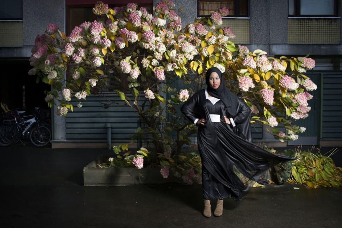 """Heidi Piiroinen kertoo kuvastaan näin: """"Naapurini Anisa. Ollessani kotona äitiyslomalla kolmen pienen lapsen kanssa halusin tutustua naapureihini. Olen seurannut tyttöjen kasvua kahden kulttuurin välissä: he ovat kiehtovalla tavalla suomalaisia somalialaisissa perheissä. Yksi tytöistä kuvasi kouluaineessaan elämäänsä: """"Koen itse, että ymmärrän omaa kulttuuriani ja maani perinnettä. Tuntuu kuin olisin sillan välillä ja en tietäisi kumpaan suuntaan mennä. Sellainen tunne tulee, kun olen kahden kulttuurin välissä. Hyvä juttu siinä on, että voin poimia eri kulttuureista asioita, yhdistää niitä ja käyttää elämässä. Vaikka se on sekavaa. Se tekee minusta minun."""" Kuvassa on mustiin pukeutunut tummaihoinen nainen hienon hortensiapuskan edessä."""